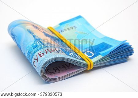 A Rolled Up Bundle Of Russian Banknotes Of 2000 Rubles Lies On A White Paper Background. Banknotes T