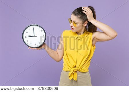 Puzzled Young Brunette Woman Girl In Yellow Casual Shirt Posing Isolated On Violet Wall Background S