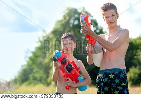 Two Kids Playing With Water Guns Outdoors. Cute Boys Spraying Water From A Gun In Backyard. Songkran