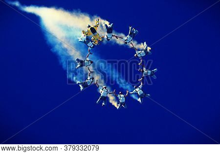 Formation of Skydivers Trailing Smoke