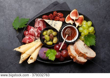 Antipasto plate with prosciutto, cheese, figs and grapes. Appetizer board. Top view flat lay