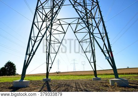 Electric pylon on field. Transmission tower with sunny sky at the background.