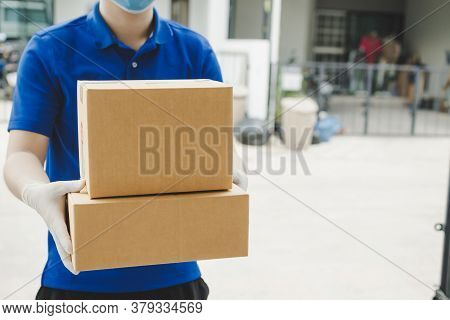 Delivery Service Man With Face Mask Waiting For Sending Parcel Post Box To Customer At Door Home, Ca