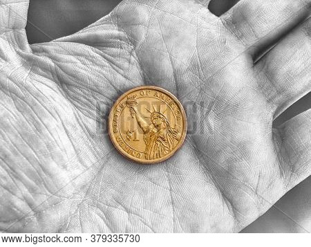 American 1 One Dollar Coin Lies On A Dirty Palm Close Up. An Impressive, Dramatic Black And White Sh
