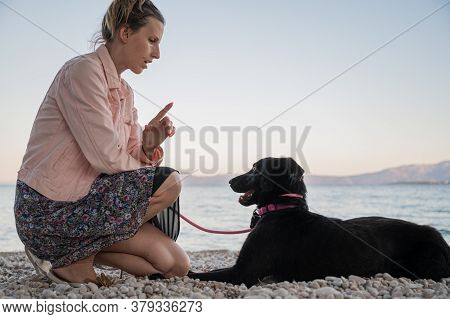 Young Woman Kneeling Down To Give Command To Her Black Shepherd Dog On Beautiful Pebble Beach.