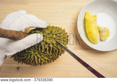 Top View Closeup Durian Peeling On The Table Wooden With Durian In Dish. Hand Of Person Wearing Glov
