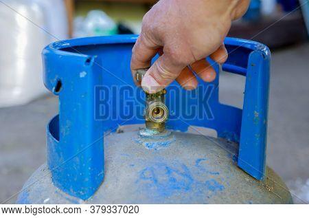Caucasian Man Opening The Valve On Blue Propan Butan Gas Tank.