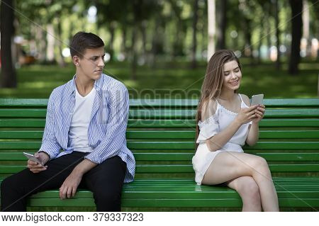 Boring Date. Pretty Girl Chatting On Phone And Ignoring Her Boyfriend At Park