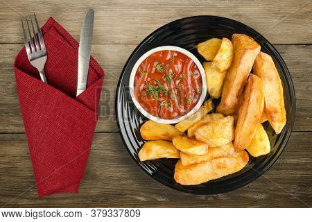 French Fries With Ketchup On Brown Wooden Background. French Fries On Black Plate With Fork And Knif