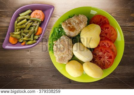 Cutlet With Potatoes On Lime Plate With Vegetable Salad Top View. Cutlet With Potatoes On Brown Wood