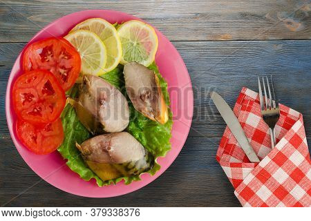 Smoked Mackerel On A Pink Plate With Fork And Knife Top View. Mackerel With Lemon And Tomato On Blue