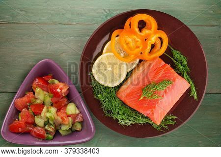 Red Fish Trout Fillets On A Brown Plate With Vegetarian Salad Top View. Fish Trout On A Green Wooden