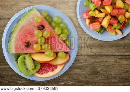 Sliced Fruit On A Brown Wooden Background. Sliced Fruit On A Light Blue Plate Top View
