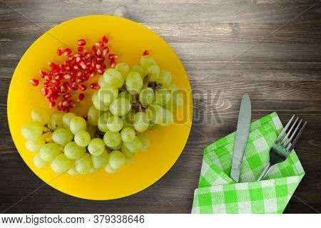 Grapes, Pomegranate On A Black Wooden Background. Grapes, Pomegranate On A Yellow Plate With Fork An