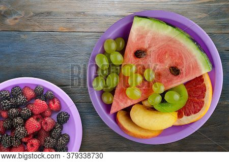 Sliced Fruit On A Blue Wooden Background. Sliced Fruit On A Purple Plate