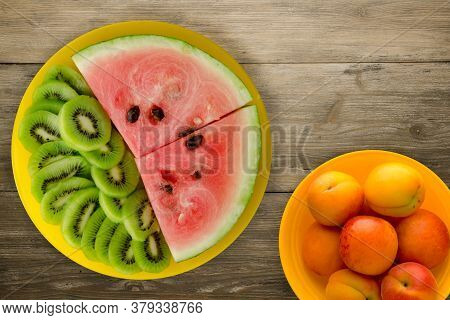 Watermelon And Kiwi Sliced On A Yellow Plate On A Brown Wooden Background.watermelon And Kiwi Sliced
