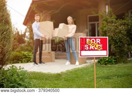 Young Couple With Boxes In Front Of Their New House On Moving Day, Focus On For Sale Sign. Copy Spac
