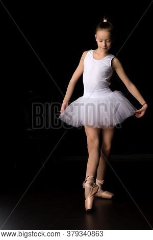 Charming Little Girl In A Bundle And Pointe Shoes Is Dancing In The Studio. Isolated On A Black Back
