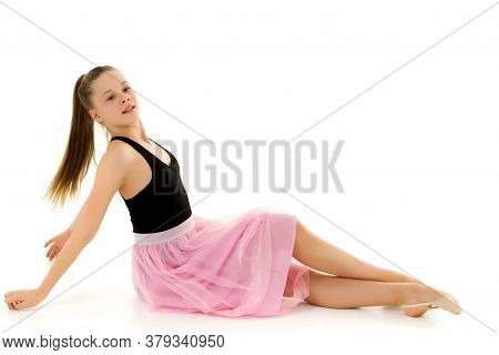 Cute Blonde In A Stylish Dress From Tulle Sitting On The Floor On A White Background, A Charming Lon