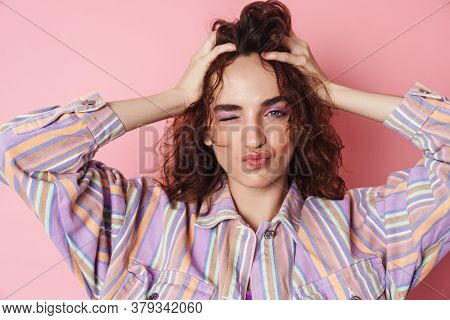 Image of redhead seductive woman winking while grabbing her head isolated over pink background