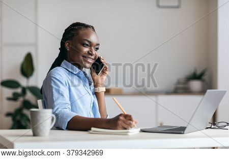 Millennial Black Woman Manager Taking Notes And Talking On Cellphone At Workplace In Office, Speakin