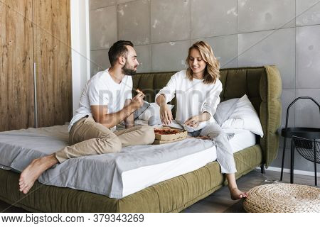 Photo of a young optimistic happy loving couple relaxing on a bed in bedroom indoors at home while eating pizza