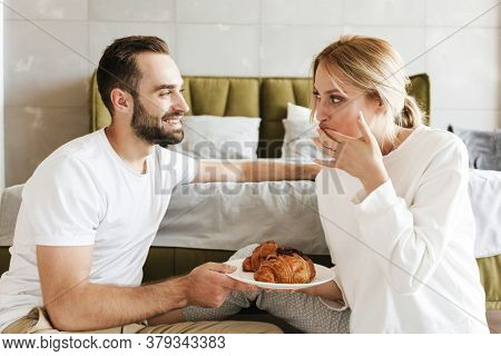Image of a young smiling optimistic loving couple relaxing indoors at home while eating croissants