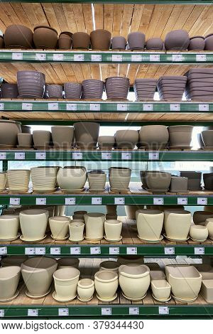 Flower Pots Are Sold At The Store. Rows Of Different Beige And Purple Pots For Indoor Plants On Shel