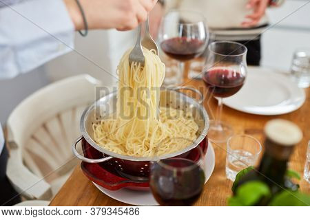 Fresh spaghetti are served at the sieve dining table for a meal together