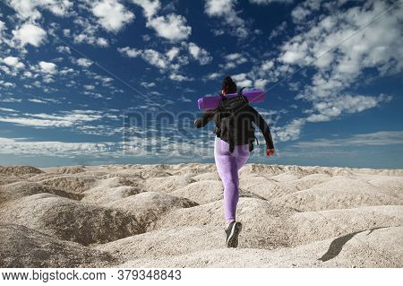 Young Woman Half-face One Tourist Running, Rear View On Hill Area In Sportswear And With Backpack Lo