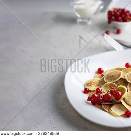Tiny Pancake Cereal On White Plate Served With Red Currant Berries And Ingredients On Grey Cement Ta