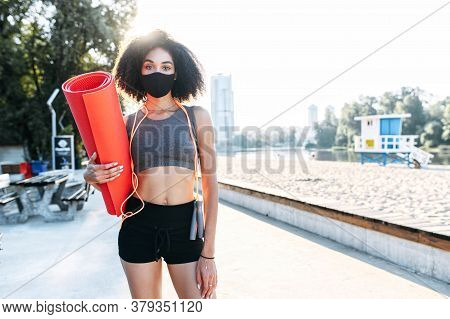 A Young African-american Woman With A Protective Medical Mask On The Face Going To Do Outdoor Workou