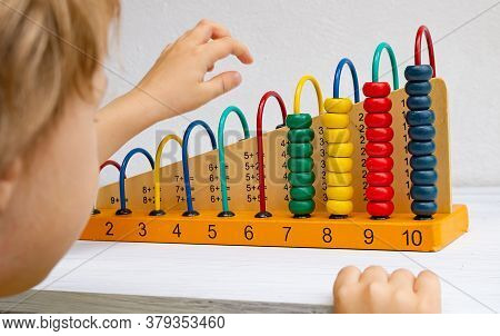 Abacus For Children, Learning Mathematics And Addition. Child Playing With Abacus On White Table.