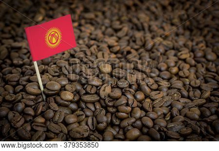 Kyrgyzstan Flag Sticking In Roasted Coffee Beans. The Concept Of Export And Import Of Coffee