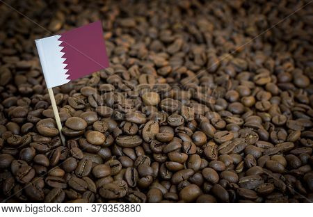 Qatar Flag Sticking In Roasted Coffee Beans. The Concept Of Export And Import Of Coffee