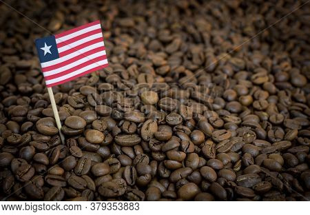 Liberia Flag Sticking In Roasted Coffee Beans. The Concept Of Export And Import Of Coffee