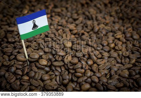 Lesotho Flag Sticking In Roasted Coffee Beans. The Concept Of Export And Import Of Coffee
