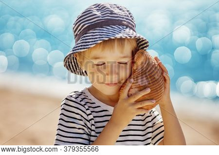 Little Boy Smiling At The Beach In Hat Andholding Shell