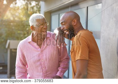 Senior Father Talking And Laughing With Adult Son In Garden At Home