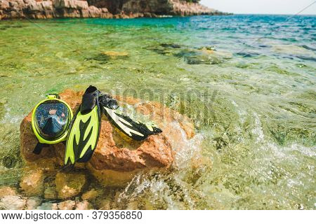 Snorkeling Mask With Flippers At Rock In Sea Water