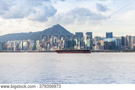 Hong Kong Bay At Sunny Day. Bulk Carrier Ship Is Moored Near Hong-kong Island