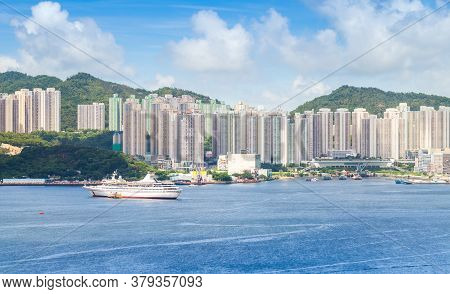 Hong Kong City At Sunny Day. Passenger Ship Moored Near Yau Tong District Of Hong-kong Island