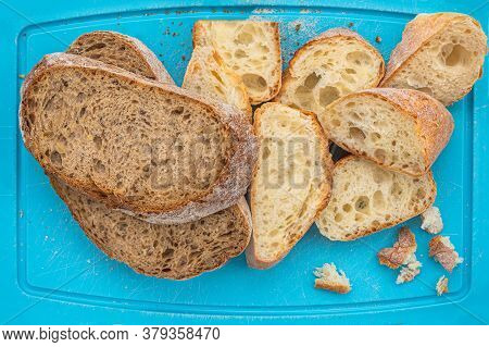 Top View Of Various Sliced Bread Ciabatta  On Cutting Board Closeup.