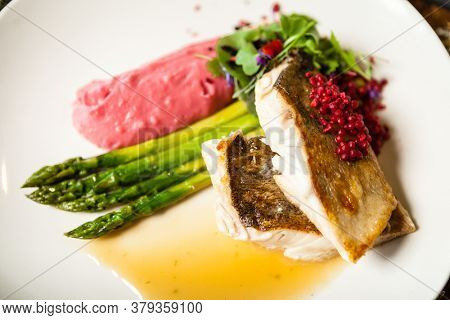 Pike-perch fillet. Asparagus, pearl couscous, white wine sauce, beet-flavored mashed potatoes. Delicious seafood fish closeup served on a table for lunch in modern cuisine gourmet restaurant.