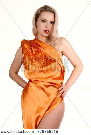 Young Stunning Tanned Blonde Woman With Long Curly Hair Wearing Orange Tunic Dress Posing At Camera