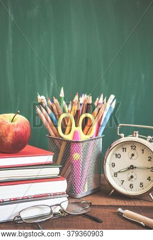 School Supplies, Alarm Clock, Apple And Books On Wooden Table In Front Of The School Chalkboard. Bac