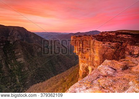 Red Sunset Over Kanagra Walls Located In Kanangra Boyd National Park.  A Woman Stands On The Edge Sh