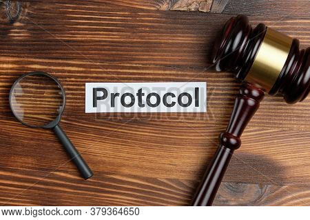 Concept Of A Court Document As A Protocol Next To The Judge Magnifying Glass And Hammer.