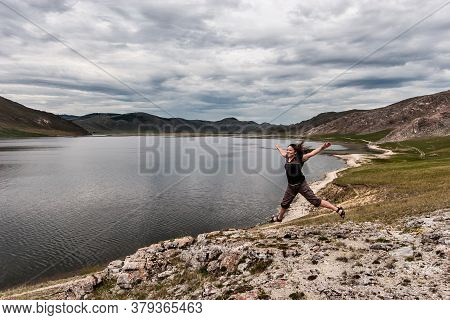 A Young Girl Laughs And Joyfully Jumps On A Rock Near The Lake. Beautiful Mountains In The Backgroun
