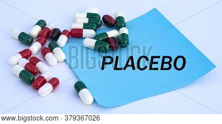 Placebo Words On A Blue Sheet Of Paper Against The Background Of Multicolored Tablets. Medical Conce